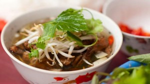 grilled pork noodle soup is served with a plate of white rice noodle ...